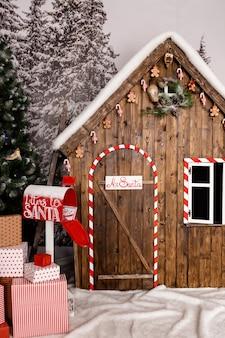 Noworoczna strefa ze śniegiem w pobliżu drewnianego domu z zabawkami.