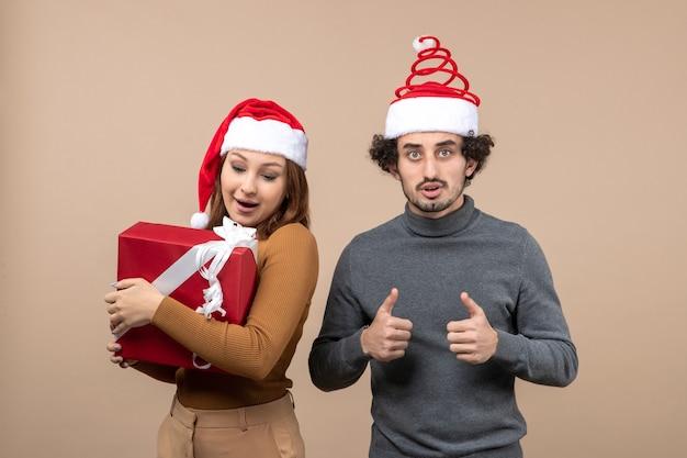 Noworoczna świąteczna koncepcja nastroju ze śmieszną uroczą parą w czerwonych czapkach świętego mikołaja na szarym materiale