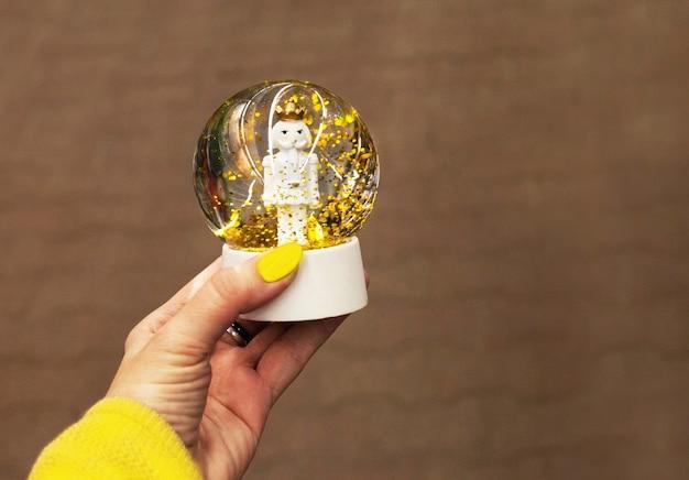 Noworoczna szklana kula z dziadkiem do orzechów w ręku z żółtym manicure, na ciemnym tle