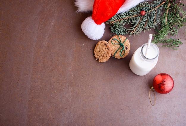 Noworoczne ciasteczka dla mikołaja z mlekiem, w białych daniach iz czekoladą. czapka mikołaja, zabawki na choinkę, gałązki choinkowe. leżał na płasko