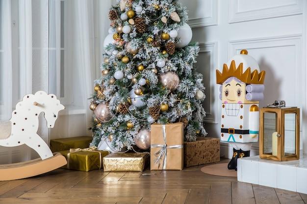 Noworoczne drzewo ozdobione prezentami i prezentami, konik na biegunach i dziadek do orzechów