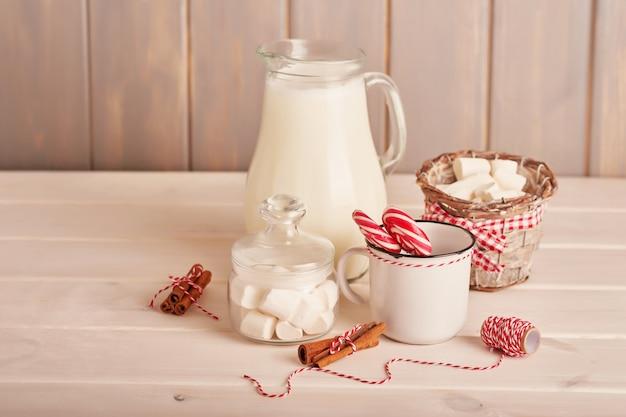 Noworoczne słodycze ptasie mleczko, lizaki i mleko na stole z prezentami