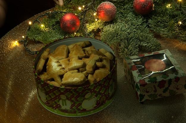 Noworoczne świąteczne ciasteczka z ozdobami świątecznymi i gałązką jodłowej żarówki