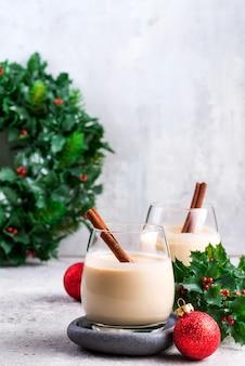 Noworoczny lub świąteczny koktajl ajerkoniakowy, gorący zimowy lub jesienny napój z cynamonem i gałką muszkatołową w szklance na jasnym kamieniu, świąteczna dekoracja