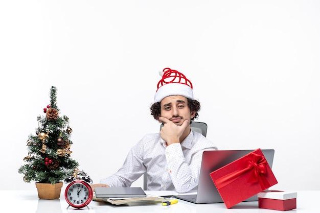 Noworoczny nastrój z burzą mózgów młody biznesmen z zabawnym czapką świętego mikołaja myślący głęboko w biurze na białym tle