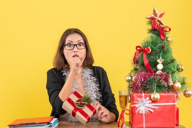 Noworoczny nastrój z piękną biznesową damą w garniturze w okularach i pokazującą jej niespodziankę siedzącą przy stole w biurze