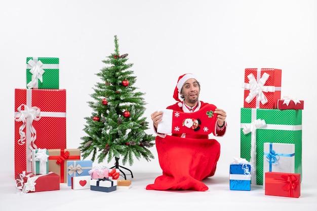 Noworoczny nastrój z zabawnym pozytywnym świętym mikołajem siedzącym na ziemi i trzymającym świąteczną skarpetę w pobliżu prezentów i zdobionej choinki na białym tle