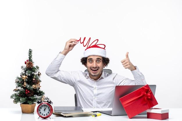 Noworoczny nastrój z zaskoczonym, uśmiechniętym młodym biznesmenem dotykającym jego zabawny kapelusz świętego mikołaja, wskazując powyżej w biurze na białym tle