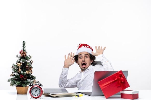 Noworoczny nastrój z zszokowanym nerwowym młodym biznesmenem w kapeluszu świętego mikołaja siedzi w biurze i pracuje samotnie nad projektem na białym tle
