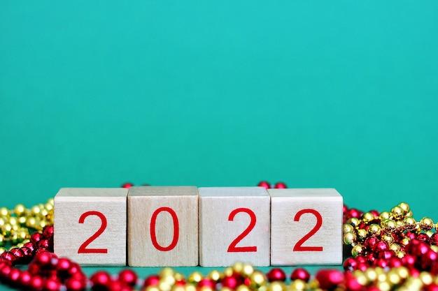 Noworoczny numer 2022 w czerwonych numerach na drewnianych klockach wśród świątecznych koralików.