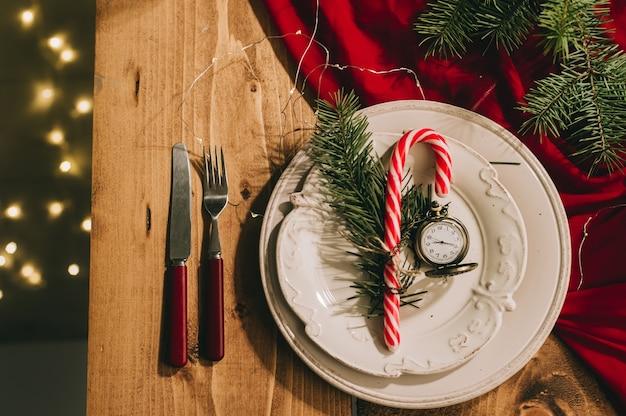Noworoczny stół z czerwonym obrusem, antycznymi naczyniami i zabytkowym zegarem.