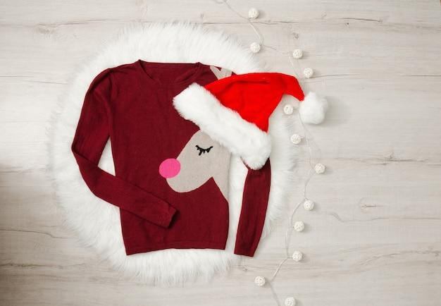Noworoczny sweter koncepcyjny z reniferem i czapką mikołaja. girlanda, tło drewna, miejsce na tekst