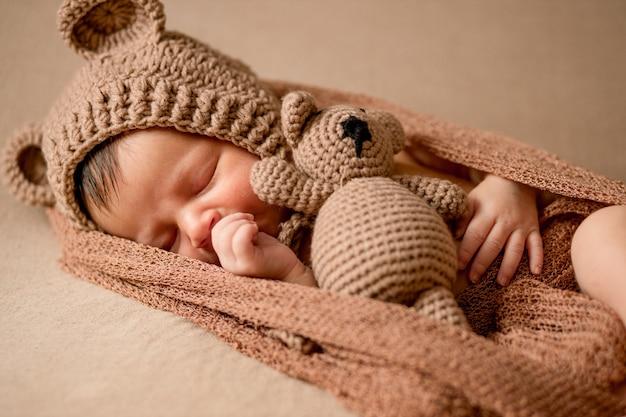 Noworodek, 10 dni, śpi w przytulnym stroju misia oraz w jasnobrązowym stroju. trzyma małego misia. początek życia i koncepcja szczęśliwego dzieciństwa.