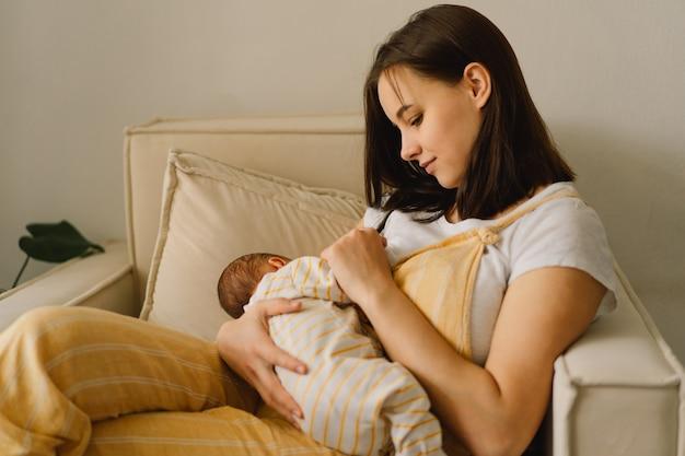 Noworodek chłopiec ssący mleko z piersi matki. portret mamy i dziecka karmiącego piersią. pojęcie zdrowego i naturalnego żywienia dziecka karmiącego piersią.