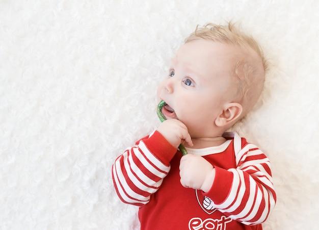 Noworodek do pięciu miesięcy w czerwonej piżamie leży na białym łóżku i gryzie cukierki