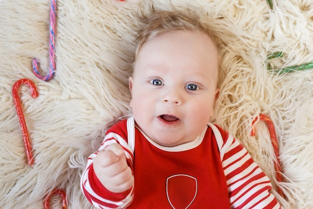 Noworodek do pięciu miesięcy w czerwonej piżamie leży wśród wielobarwnych zwierzeń