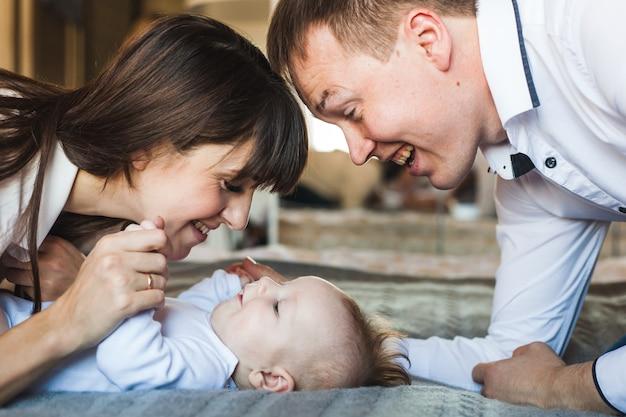 Noworodek leżący na łóżku, mama patrzy na swoje dziecko, tata patrzy na swoje dziecko, mały chłopiec