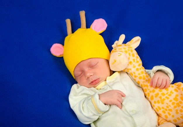 Noworodek leżący na niebieskim kocu z zabawkową żyrafą. chłopiec czy dziewczyna