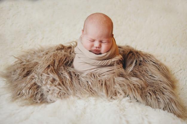 Noworodek owinięty w koc śpi w koszu. dzieciństwo, opieka zdrowotna, ivf.