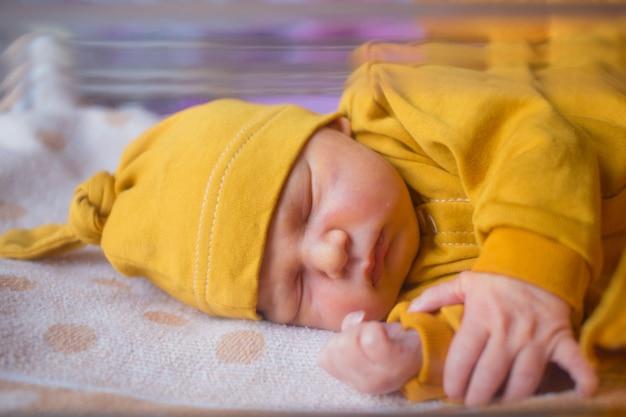Noworodek płci męskiej śpi spokojnie w środku