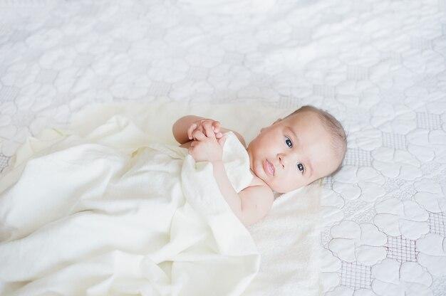 Noworodek relaksujący się w łóżku po kąpieli lub prysznicu.