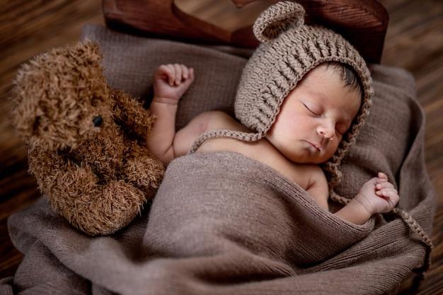 Noworodek, śliczne niemowlę, leży i trzyma malutkiego misia w łóżeczku na drewnianym.