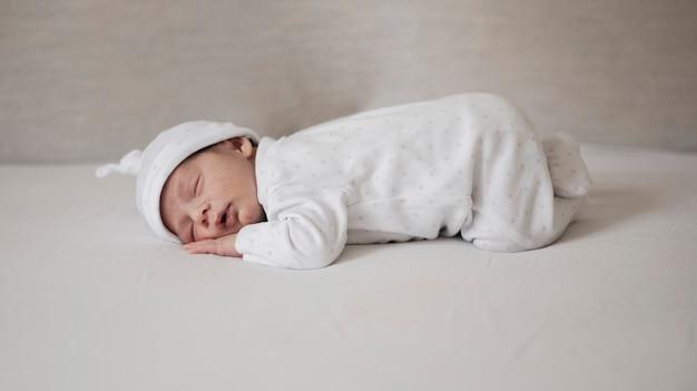 Noworodek śpi na białych prześcieradłach