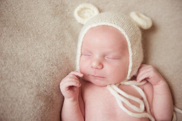 Noworodek śpi na łóżku w białym kapeluszu z uszami