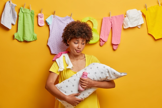 Noworodek śpi na rękach matki. zdziwiona kobieta trzyma dziecko zawinięte w ręcznik, butelkę z mlekiem, opiekuje się niemowlęciem, nie może zrozumieć, dlaczego córka płacze, zajęta pracami domowymi