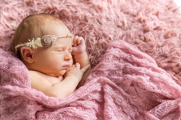 Noworodek śpi na różowym tle. selektywna ostrość. ludzie.