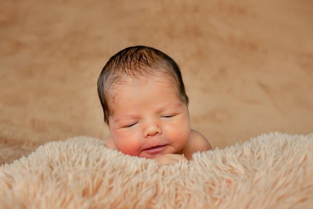 Noworodek śpi, spoczywa na własnych rękach i łokciach, na brązowym tle