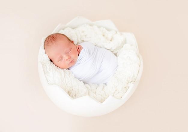 Noworodek śpi w kołysce w kształcie jajka