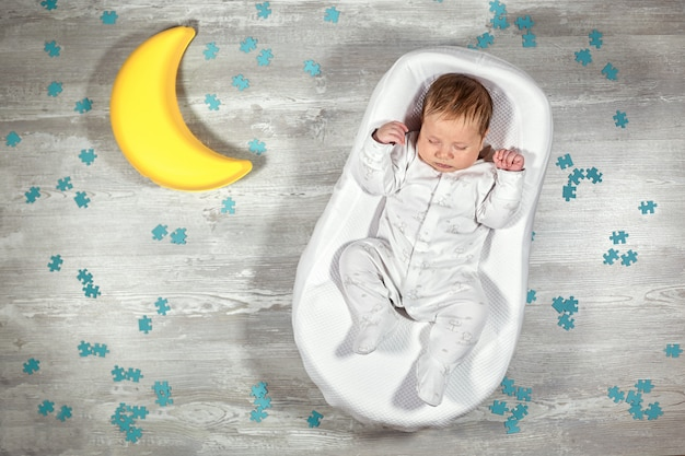 Noworodek śpi w specjalnym materacu ortopedycznym kokon dziecięcy, na drewnianej podłodze, zabawkowy księżyc i puzzle. spokojny i zdrowy sen u noworodków.
