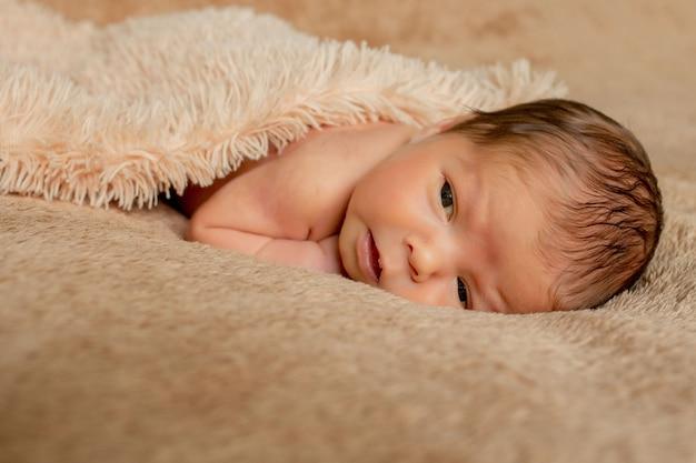 Noworodek śpi, wsparty na własnych rękach i łokciach