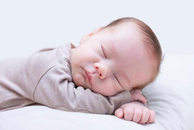 Noworodek śpiący na brzuchu na jasnym tle
