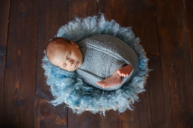 Noworodek śpiący noworodek, zawinięty w niebieski materiał, leży w koszu na niebieskim futrze