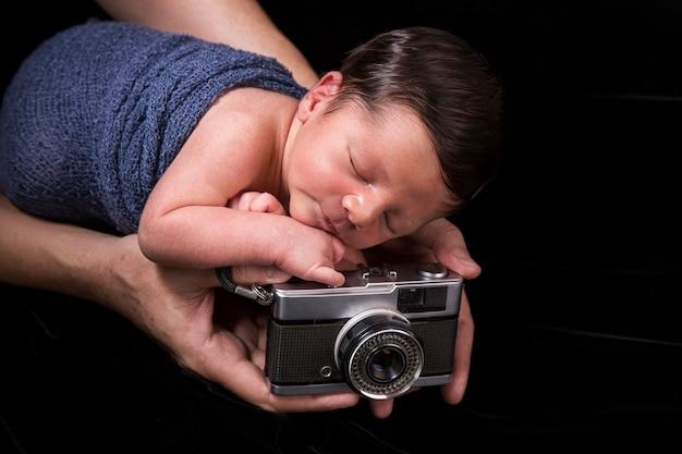 Noworodek śpiący ze starym aparatem