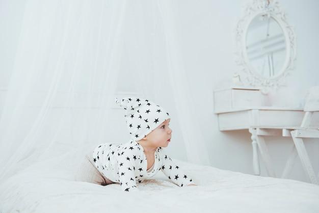 Noworodek ubrany w biały garnitur i czarne gwiazdki to białe miękkie łóżko w studio