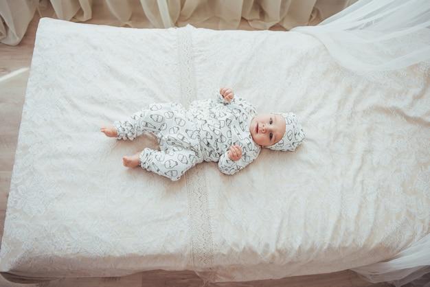 Noworodek ubrany w garnitur na miękkim łóżku. widok z góry