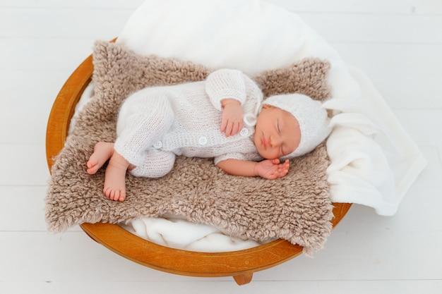 Noworodek w białym kostiumie króliczka śpi na drewnianym koszyczku