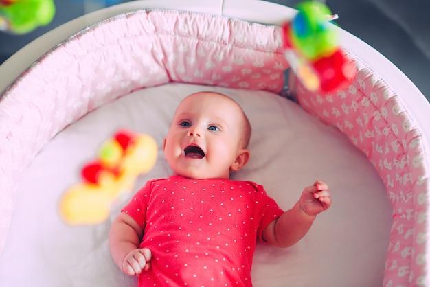 Noworodek w czerwonych ubraniach z bosymi stopami leży w białym łóżeczku i patrzy na zabawki