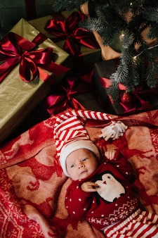 Noworodek w czerwonym stroju bożonarodzeniowym leży pod choinką z prezentami