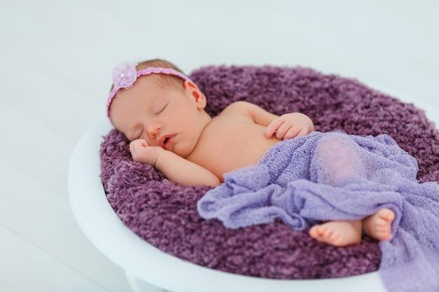 Noworodek w fioletowym garniturze śpi w drewnianym koszyku
