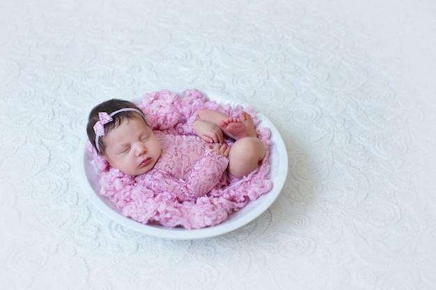 Noworodek w kolorze różowym śpi