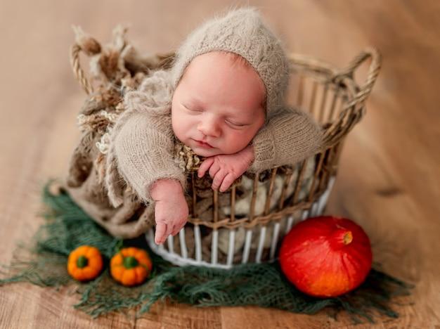 Noworodek w koszyku obok dyni