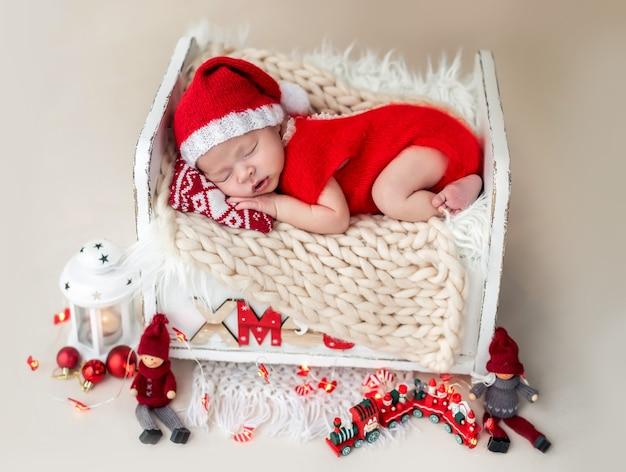 Noworodek w stroju mikołaja leżący na łóżku