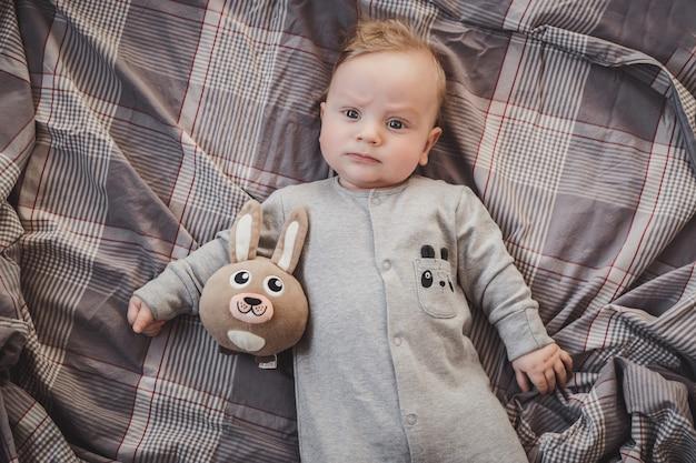 Noworodek w wieku do czterech miesięcy leżący na łóżku z zabawkowym zającem
