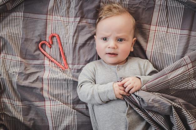 Noworodek w wieku do czterech miesięcy leżący na szarym łóżku obok czerwonego serca