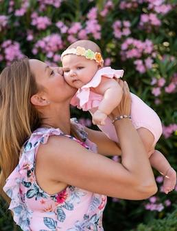 Noworodka dziewczynka w różowych ubraniach z dzianiny i akcesorium na głowę w ramionach kobiety