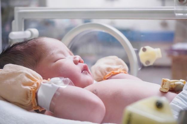 Noworodka dziewczynka wewnątrz inkubatora w szpitalu po porodzie